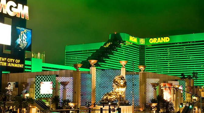 The beatufiul MGM Grand Hotel and Casino at night against a neon-lit sky.